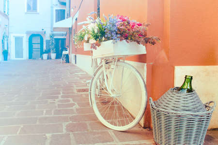 Decorative mediterranean bicycle. White bike with flowers and a flask of wine (copy space available on the left)