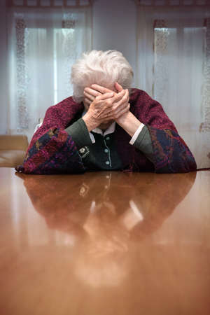 Pain of an old woman, disconsolate lonely senior female at home (unrecognizable person)
