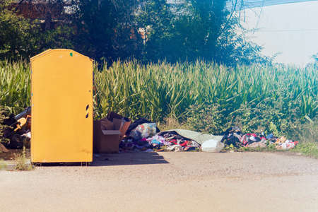 Charity clothes waste. Second hand stuff abandoned on the ground and a yellow donation box on the left