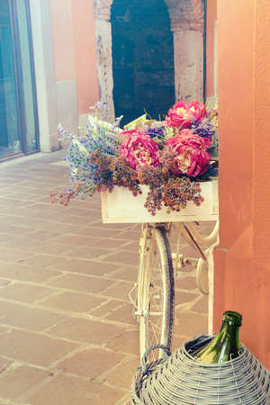 Old-fashioned bike street decoration. Vertical picture, detail of mediterranean culture with ancient architectures on the background