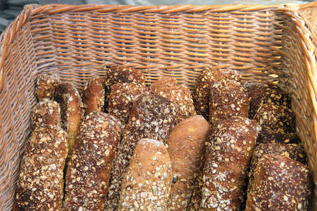 Wholegrain bread in a basket. Baked baguettes topped with different seeds Фото со стока