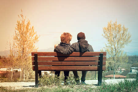 middle-aged lovers date, back view of two people sitting on a bench in the park