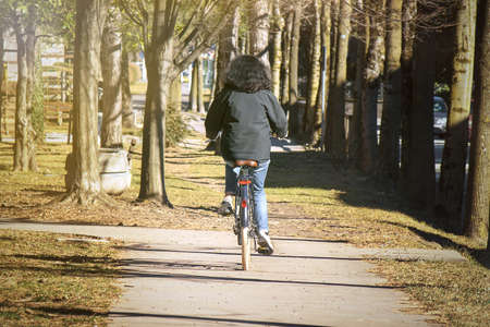 Lady cycling in the park. Back view of woman with black hair riding a bike