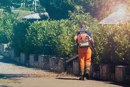 Worker with leaf blower, man operating a tool to clean the street (the leaves swirled up)