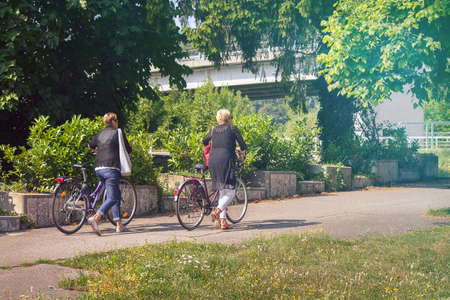 Ladies with bikes in a city park, two middle aged women carry bicycles along the road (unrecognizable people)