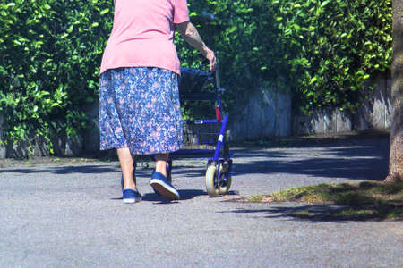 Walking Frame with Wheels. Detail of a lady human legs pushing a walker on the street