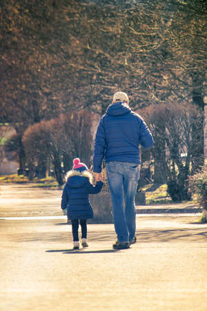 fatherhood concept, little girl walking with dad (parenthood, family, or adoption concept)