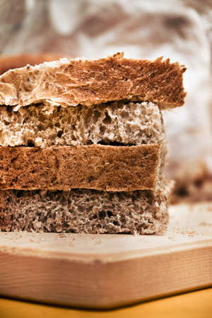 detail of brown bread, closeup of Sliced whole wheat food on a wooden chopping board (vertical picture)
