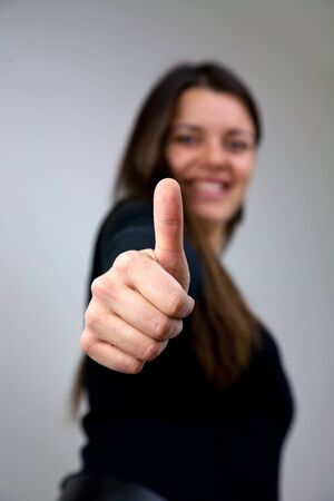 dark haired: Dark haired girl with thumb up smiling