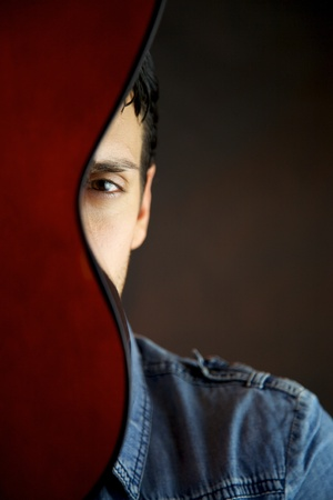 Male model behind guitar portrait photo