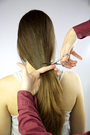 cutting very long brunette hair Stock Photo