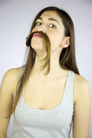 Funny girl making mustache with her very long hair Stock Photo