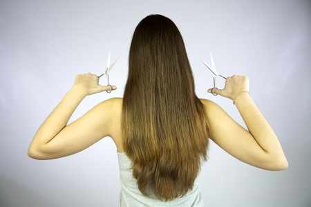 Girl with 2 pairs of scissors ready to cut her long hair Stock Photo