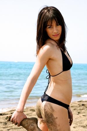 woman in bikini on sea  with foot in hand full of sand photo
