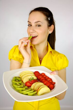 gorgeous brunette female model with plate full of fruit photo
