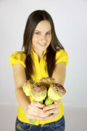 Female model with artichokes in her hands and yellow shirt photo
