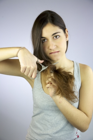 Girl cuts all her long hair with scissors unhappy of it photo