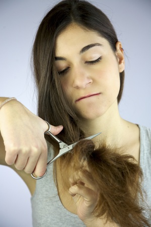 girl cuts her long hair very unhappy and angry Stock Photo - 13135026