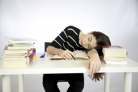 hard working woman: Lazy girl falls asleep while studying surrounded by books