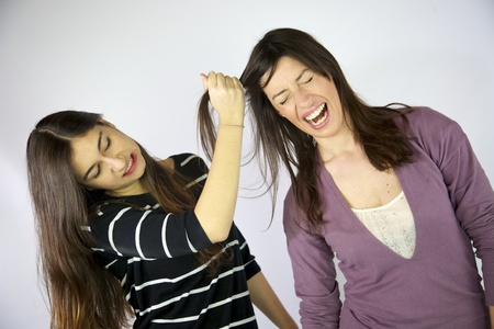 Girl pulling hard long hair of her friend photo