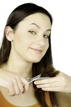 Female model happy about cutting her long hair with scissors Stock Photo - 13644308