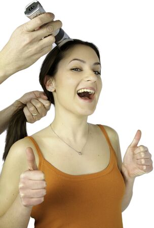 Hairdresser buzzing long hair of happy female model with thumbs up Stock Photo - 13644309