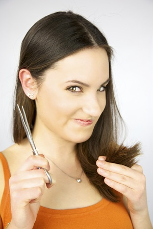 Girl with scissors ready to cut hair making very weird face Stock Photo - 13644312
