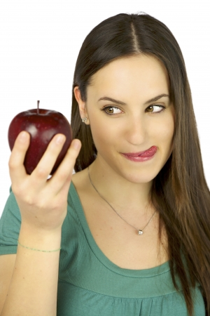Young female model observing intense a big red apple ready to eat it photo