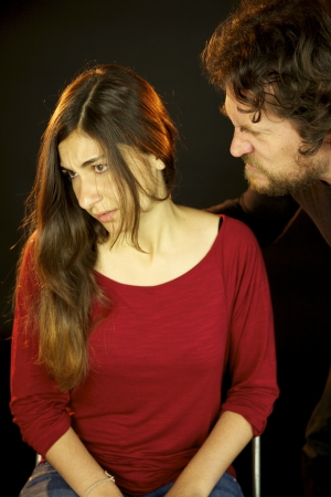 Young woman depressed attached by scary man with beard in the dark