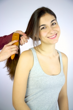 Young girl smiling while hairdresser brushes her long silky hair Stock Photo - 13851021