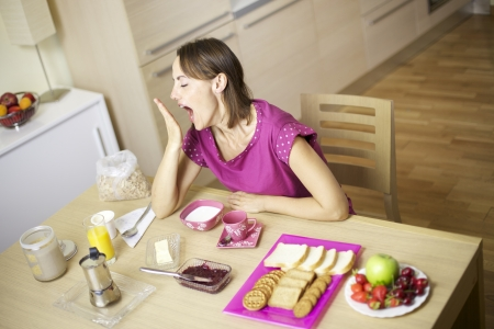 Woman yawning with hand in front of open mouth photo