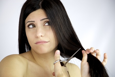 woman with long black hair cutting it with scissors