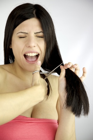 Beautiful female model cutting her long hair with sharp scissors scared photo