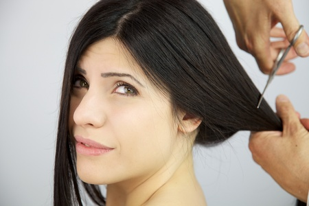 Female model with worried expression because her hair is being cut by hairdresser Stock Photo - 14403092