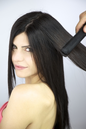 Hairdresser ironing long brunette silky hair Stock Photo