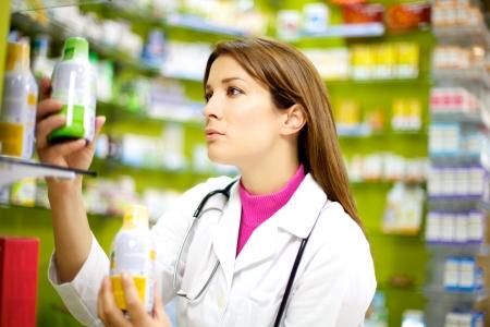 의학: 약으로 그녀의 약국에서 주문을 넣어 젊은 좋은 찾고 의사 스톡 사진