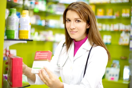 happy doctor working in pharmacy with medicine in her hand