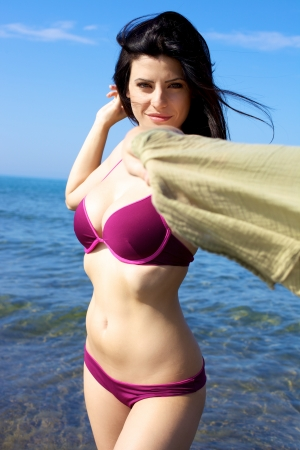 Gorgeous young woman happy in the blue sea photo