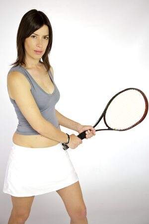 Beautiful woman ready to hit the ball with racquet playing tennis photo