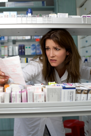 Beautiful woman pharmacist looking for medicine worried
