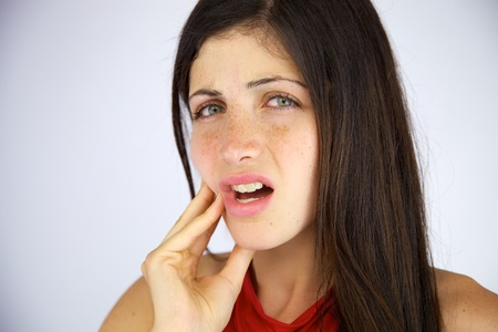 pained: Gorgeous female model suffering bad toothache closeup