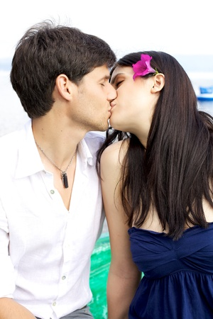 Happy couple kissing on a boad on a lake