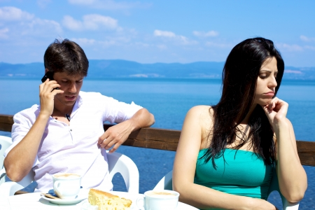 Handsome man on the phone girlfriend angry having breakfast on a lake Stock Photo