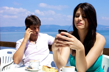Woman texting man talking on cellphone during breakfast on a lake