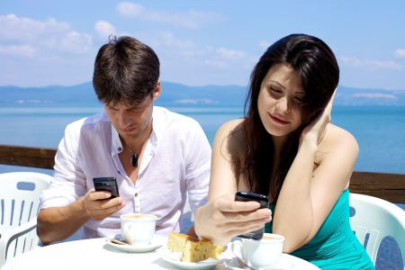 Happy couple texting with mobile phone during breakfast with cappuccino and cake on the lake Stock Photo