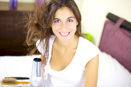 Smiling cute girl dry her hair at home in bed photo