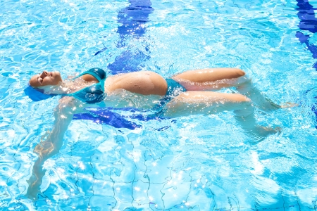 Happy relaxed pregnant woman swimming happy in beautiful swimmingpool Stock Photo