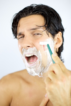 Man bleeding while shaving face with blade scared photo