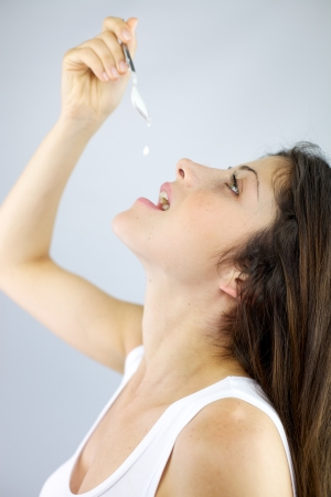 Beautiful female model eating one drop of yogurt with spoon  photo