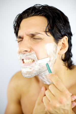 Handsome man fear of shaving with blade